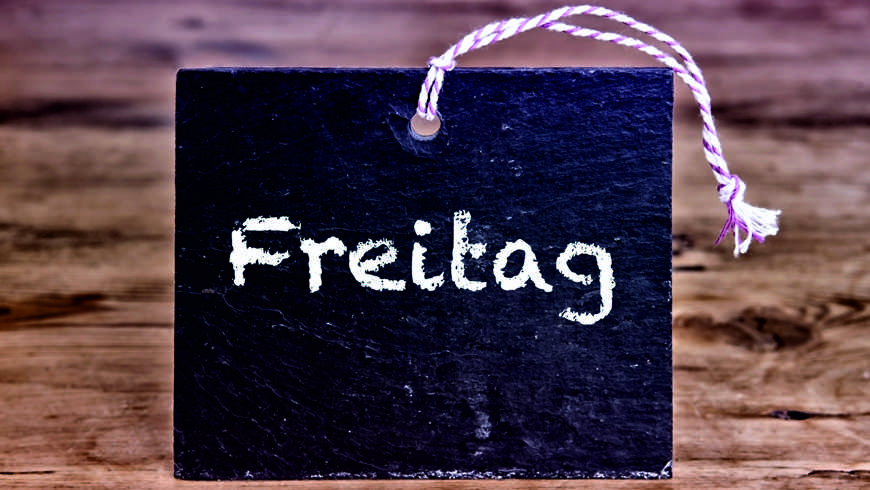 the german word for Friday written on chalk board on wooden table