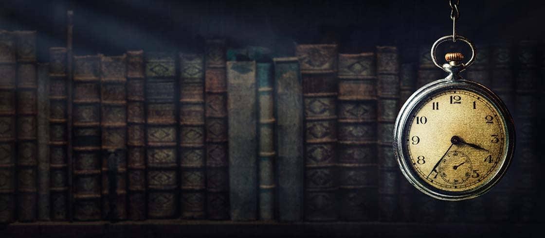 Im Dunkel des Hintergrunds alte Bücher, im Vordergrund eine alte Taschenuhr mit Patina