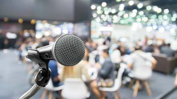 Microphone with abstract blurred photo of conference hall or seminar room with attendee and bokeh, Business meeting concept