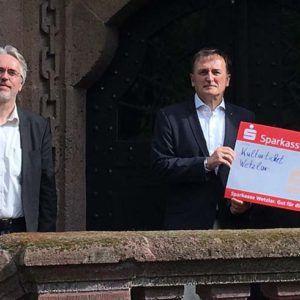 Spendenscheckübergabe durch Martin Marx an Sigrid Kornmann, begleitet von (v.l.) Karl-Ludwig Kreuzburg und Frank Mignon