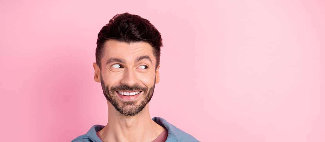 Photo of dreamy charming young happy man look empty space good mood isolated on pink color background.