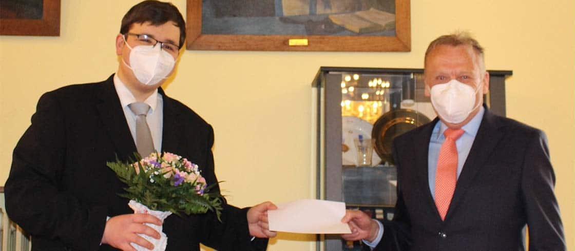 Der Meister vom Stuhl, Lennart Steen (rechts), übergibt die Förderurkunde an Chorleiter Karl Hänsel.