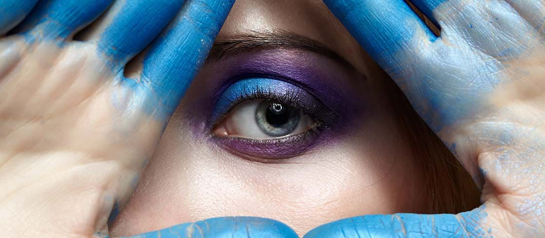 Eye of Providence, eye pyramid symbol made of hands and female face with blue paint on fingers